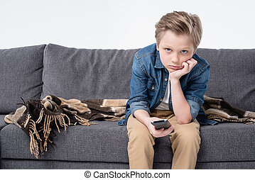 pre-adolescent bored kid boy sitting on sofa and using...