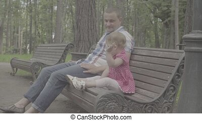Dad and little baby girl sitting on a bench