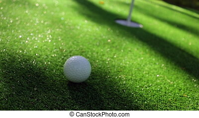 Close-up of golfer using putter to sink short putt into...