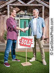 men shaking hands with saleman and buying new house