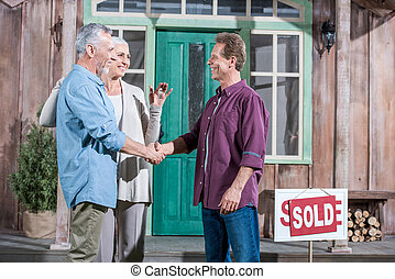senior wife holding keys of new house while her husband...