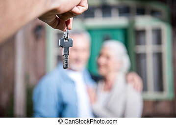saleman giving keys of new house to new owners, selective...