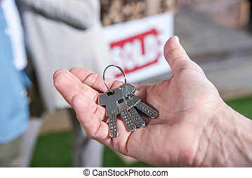 cropped view of saleman holding keys of new house, house for...