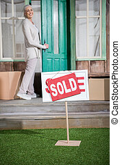 Smiling senior woman standing on porch of new house with sold sign