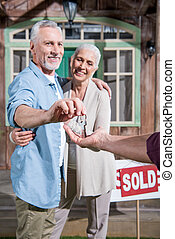 saleman giving keys of new house to happy senior couple