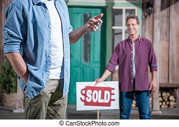 senior man buying new house and holding keys, selective...