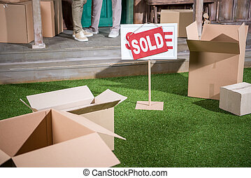 Cropped shot of couple standing on porch of new house and sold sign with cardboard boxes on grass