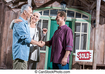 happy senior wife holding keys of new house while her...