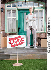 Confident senior woman with crossed arms standing on porch of new house and sold sign on green grass