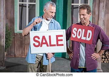 senior man holding sale sign while another man holding sold...