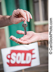 cropped view of man buying new house and taking keys, sold...