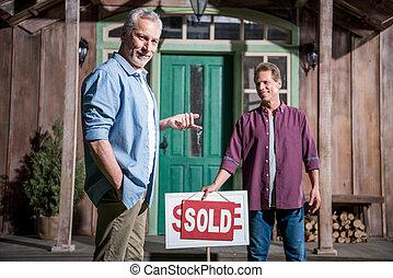 smiling senior man buying new house and holding keys