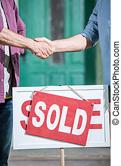 cropped view of men shaking hands with saleman and buying...