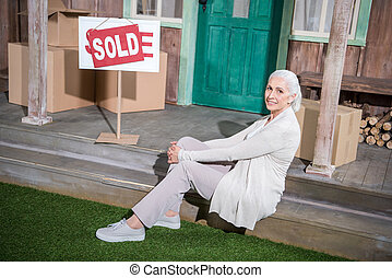 Smiling senior woman sitting on stairs of new house with sold sign