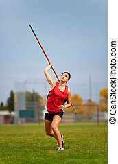 Javelin - A young, female athlete throwing a javelin in a...