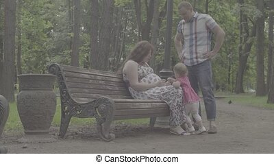 Pregnant mom and baby girl sitting on a bench