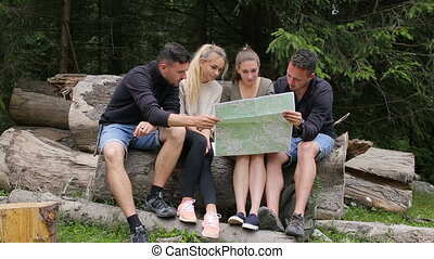 Hikers exploring the map on a fallen tree or log