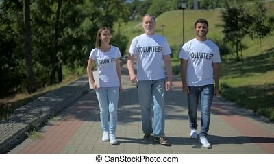 Positive group of volunteers walking along the path - Serve...