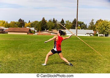 Javelin Throwing - A young, female athlete throwing a...