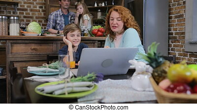 Family Make Video Call Using Laptop While Cooking Food In Kitchen Happy Parents And Children Waving Hands