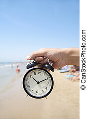 young man with an alarm clock on the beach - closeup of a...