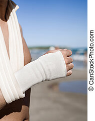 man on the beach with a bandage in his wrist - closeup of a...