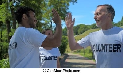Positive volunteers giving high five - Good job. Cheerful...