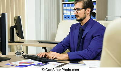 Businessman working on the computer and talking on the...