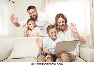 Happy family with two adorable children sitting together and...