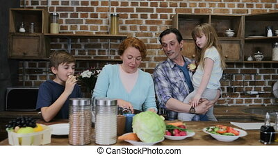 Happy Family Helping Mother With Cooking Together In Kitchen, Parents With Small Son And Daughter Preparing Food Together At Home