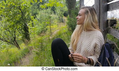 A young, beautiful girl relaxes on a mountain road near a fence and drinks water