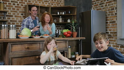 Family In Kitchen Watch Funny Videos On Tablet Computer...