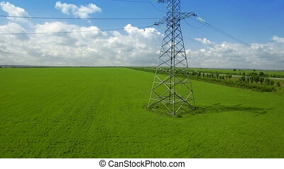 AERIAL High-voltage tower summer light sky background green...