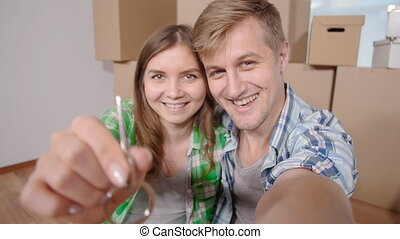 Couple showing keys to new home and selfie - Happy Couple...
