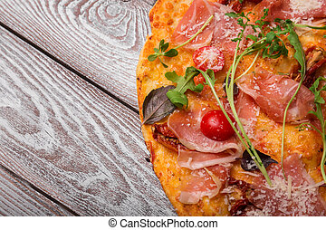 Top view of a pizza. Pizza with meat, cheese and vegetables on a wooden background. Italian cuisine concept. Copy space.