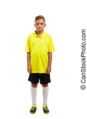 Full height of a cute boy in a yellow t-shirt, black shorts and white knee socks isolated on a white background.