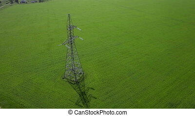 AERIAL High-voltage tower summer blue sky background green grass orbit circle panorama fly