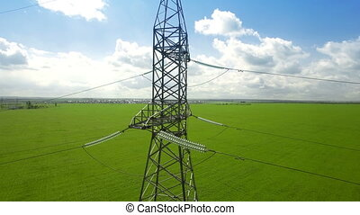 AERIAL High-voltage tower summer blue sky background green...