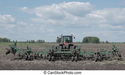 tractor preparing a seed system in the field spring