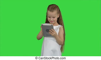 Small girl using tablet computer on a Green Screen, Chroma Key