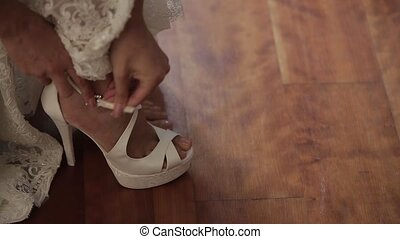 The bride wears white wedding shoes with her hands.
