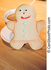 Gingerbread man with coffee on a wooden table