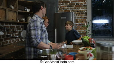 Happy Family In Kitchen Cooking Food While Son Filming Video Of Parents And Sister Preparing Meal Together