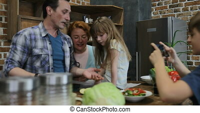 Son Making Video Of Happy Family In Kitchen Cooking Food Happy Smiling Preparing Meal Together