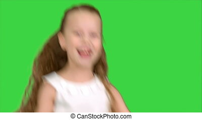 Playing, jumping little girl in white dress enjoys game on a...