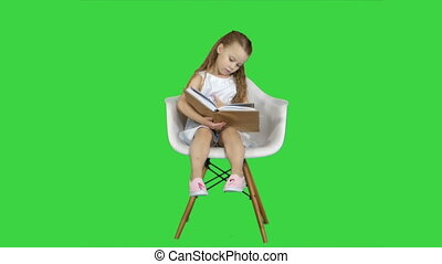 Little student girl sitting and reading book on a Green Screen, Chroma Key