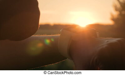 Woman using smart watch in forest at sunset - Woman using...