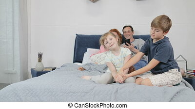 Family In Bedroom, Parents Using Cell Smart Phone While Children Play Together In Morning