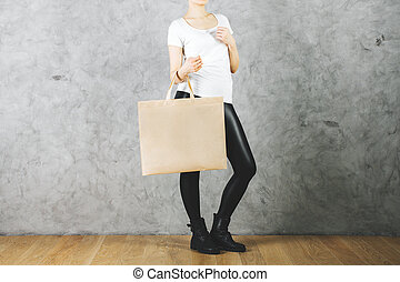 Consumerism concept - Female holding empty shopping bag on...