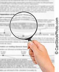 Magnifying glass in hand and business text
